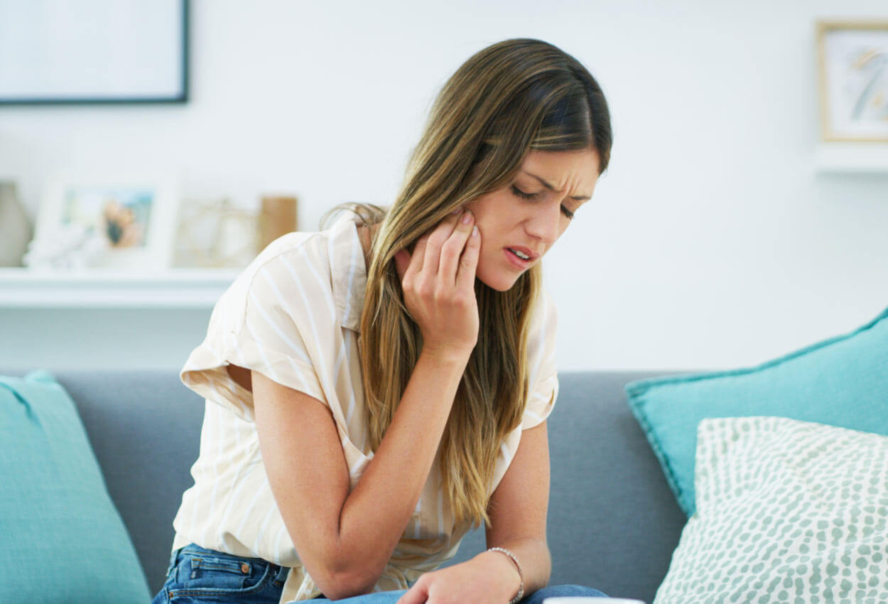 Brunette woman on a couch cringes in pain and touches her cheek due to a toothache