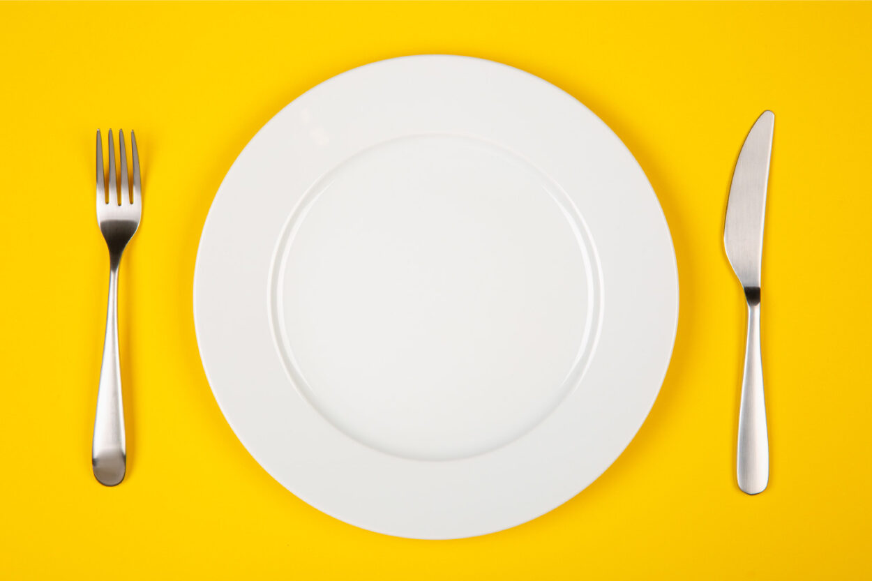 Aerial view of a white plate and silverware on a yellow background