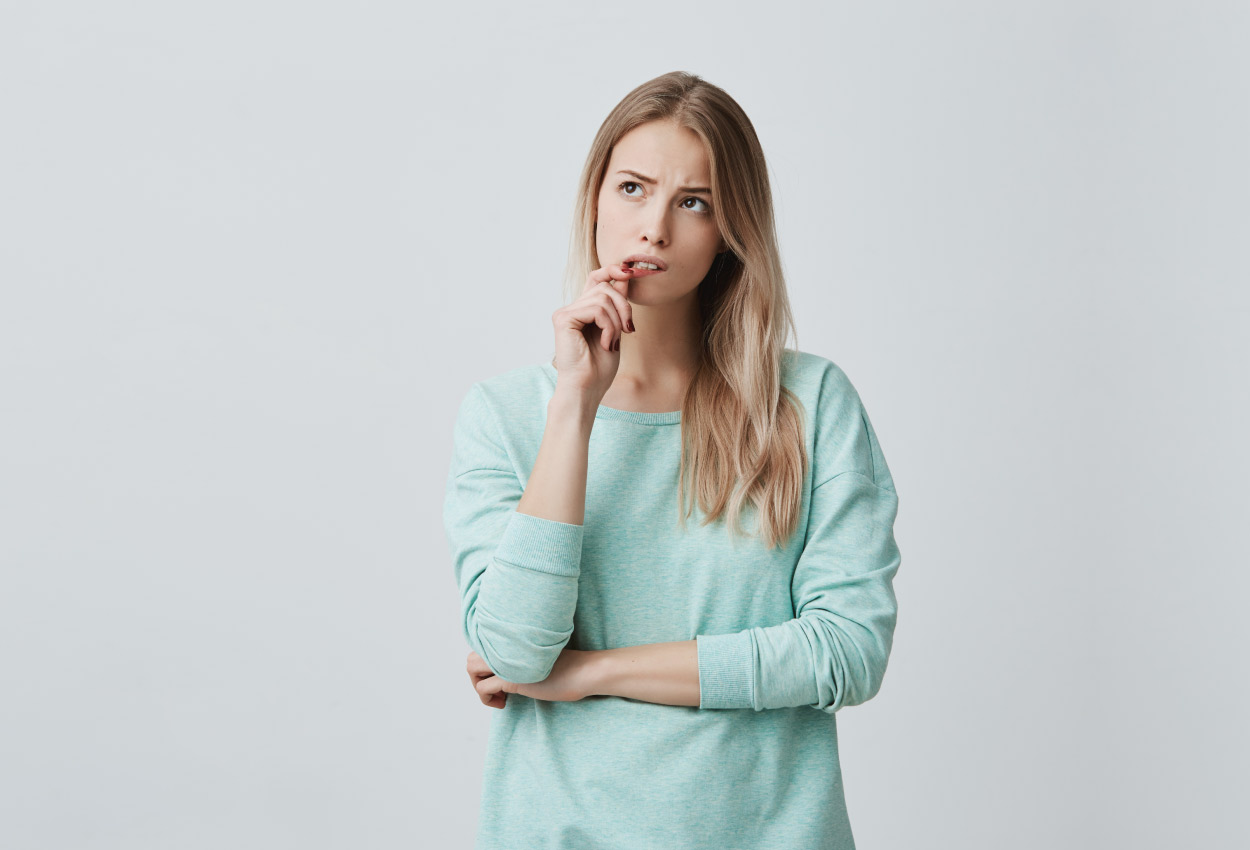 Blonde woman in turquoise shirt wonders what to do about her shifted bite and crooked teeth